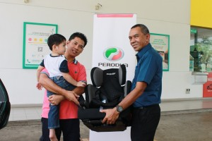 Perodua Sales Sdn Bhd Managing Director Dato' Dr Zahari Husin presents a GearUp Child Seat to a lucky motorist and his young son.