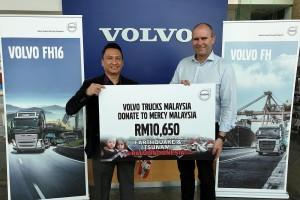 Ir. Amran Mahzan, Executive Director, Mercy Malaysia (left) receiving the mock cheque from Volvo Trucks Malaysia Managing Director, Mitch Peden.