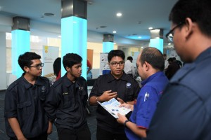 Amirul Shafiq representing Universiti Malaysia Perlis, explaining the mechanism of their vehicle design to Suria Component Manufacturing (M) Sdn. Bhd personnel.